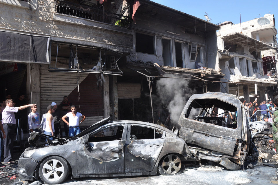 In this photo released by the Syrian official news agency SANA, Syrian citizens gather near damaged cars that were burned after a car bomb exploded in the suburb of Jaramana, Damascus, Syria, Thursday , July 25, 2013. Syria's state-run news agency says many people have been killed and scores wounded in a powerful car bomb explosion near Damascus. (AP Photo/SANA)