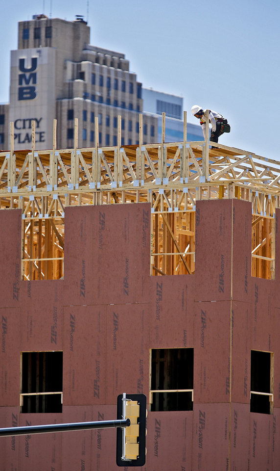 Photo - A worker frames the top floor of the 139-unit Maywood Apartments at NE 4 and Oklahoma on Monday. Phase one is well underway and leasing should start this fall. Construction on a $20 million, 160-unit second phase is set to start at NE 4 and Walnut this summer.  CHRIS LANDSBERGER