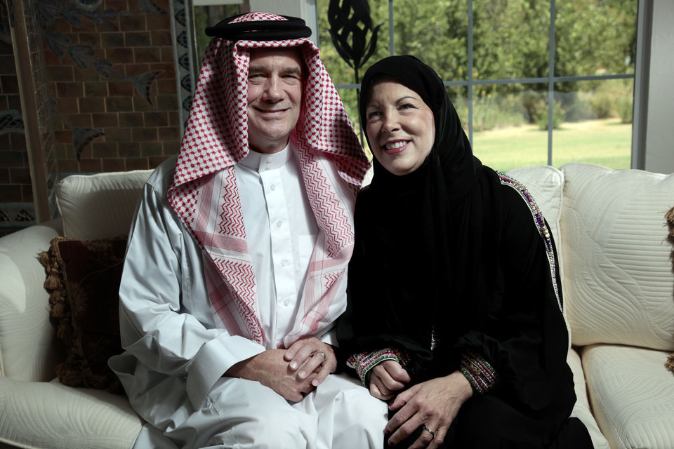 Photo - David and Carol Hartmann pose Thursday in outfits they wore in Saudi Arabia. Photo by Sarah Phipps, The Oklahoman