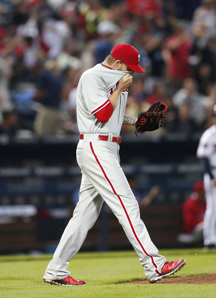 Photo - Philadelphia Phillies starting pitcher A.J. Burnett wipes his face as he walks back to the mound after giving up a two-run single to Atlanta Braves' Andrelton Simmons in the second inning of a baseball game in Atlanta, Friday, July 18, 2014. (AP Photo/John Bazemore)