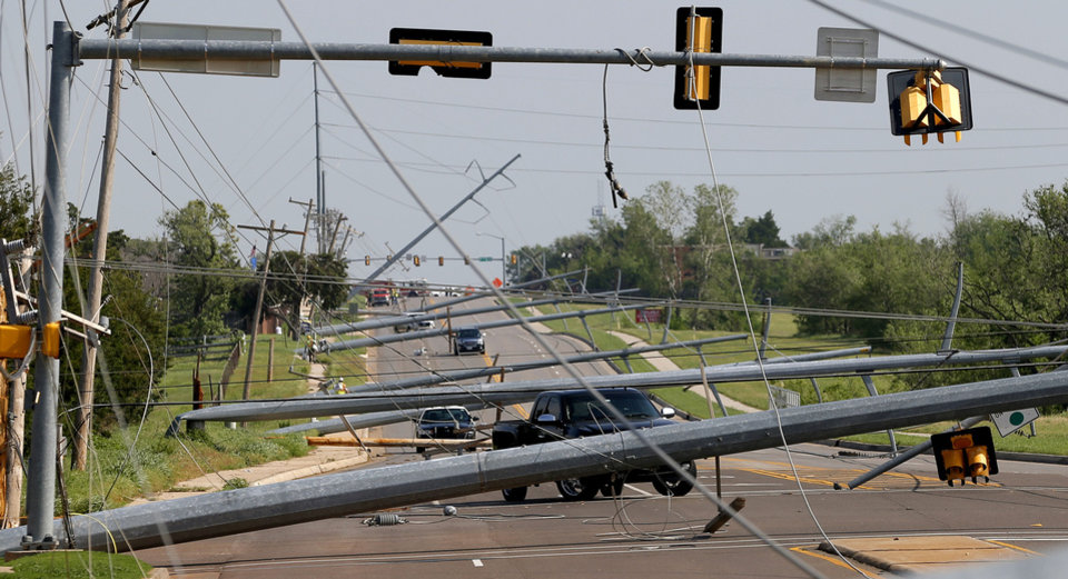 Photo - Downed utility lines trap vehicles along N Pennsylvania Avenue just north of NW 150 in Oklahoma City on May 19. Residents in nearby apartment complexes were without power and unable to drive their cars out of the area due to downed utility lines after storms moved through the area.  BRYAN TERRY - Photo by Bryan Terry, The Oklaho