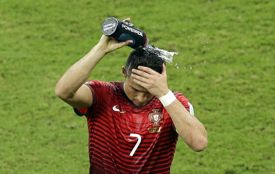 Photo - Portugal's Cristiano Ronaldo pours water over his head during the group G World Cup soccer match between the USA and Portugal at the Arena da Amazonia in Manaus, Brazil, Sunday, June 22, 2014. (AP Photo/Themba Hadebe)