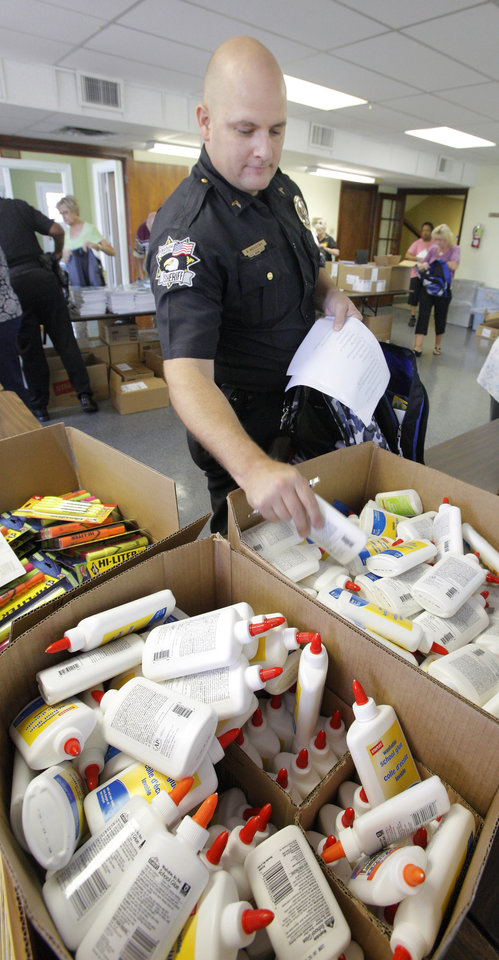 Volunteer Scott Novonty, Oklahoma County deputy sheriff, selecting a bottle of glue while putting together a backpack of school supplies at Sunbeam Family Services in Oklahoma City Monday, July 23, 2012.  Photo by Paul B. Southerland, The Oklahoman
