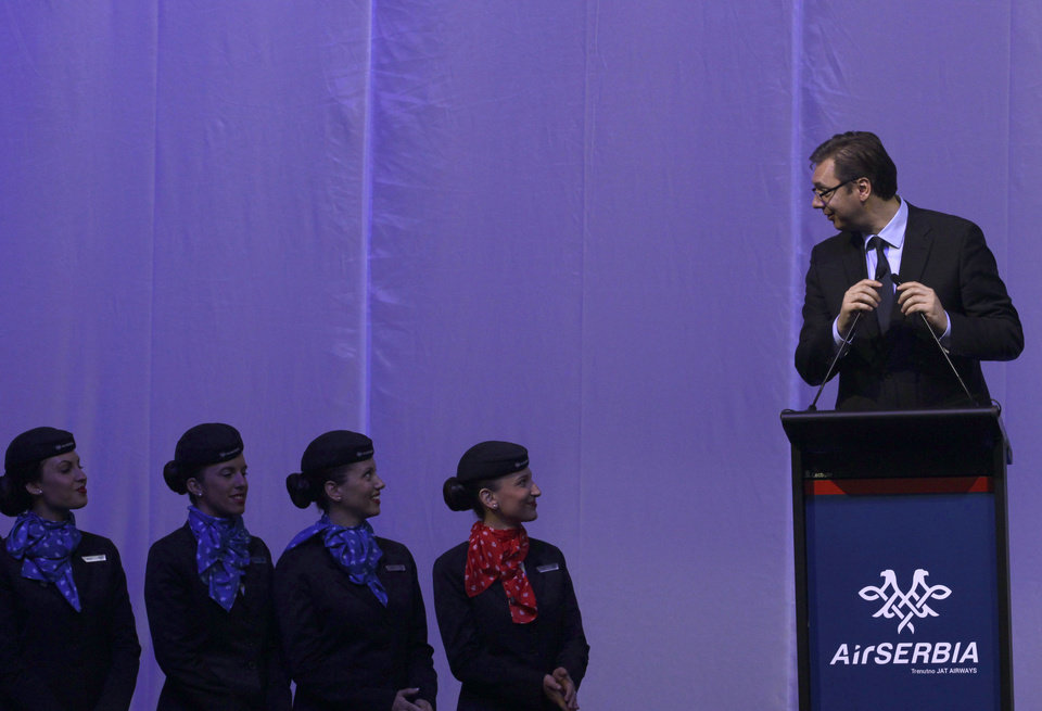 """Photo - Serbia's deputy prime minister Aleksandar Vucic, right, speaks during the inauguration ceremony of the first Airbus A319-100 aircraft in Air Serbia livery at Belgrade's Nikola Tesla Airport, Serbia, Friday, Oct. 25, 2013. Officials say that Air Serbia, Balkan country's new national carrier partly owned by Etihad Airways, formally starts flying this weekend, spelling the end for the old loss-making JAT Airways. Air Serbia's chief manager Dane Kondic said Friday that the company's inaugural flight will take place on Saturday to Abu Dhabi, United Arab Emirates. He says that """"it is an important flight that will mark a crossroads."""" Kondic and Serbia's deputy prime minister Aleksandar Vucic unveiled at a ceremony at Belgrade's airport an Airbus A319 plane bearing a double-headed eagle logo in Serbia's national, red, white and blue colors. Vucic says Air Serbia hopes to become the leading regional airline. (AP Photo/Darko Vojinovic)"""