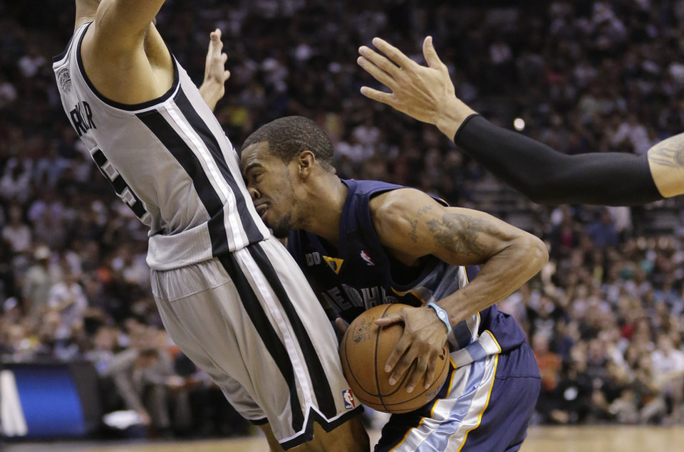 Photo - Memphis Grizzlies' Mike Conley, right, crashes into San Antonio Spurs' Tony Parker (9), of France, during the second half in Game 1 of a Western Conference Finals NBA basketball playoff series, Sunday, May 19, 2013, in San Antonio. (AP Photo/Eric Gay)