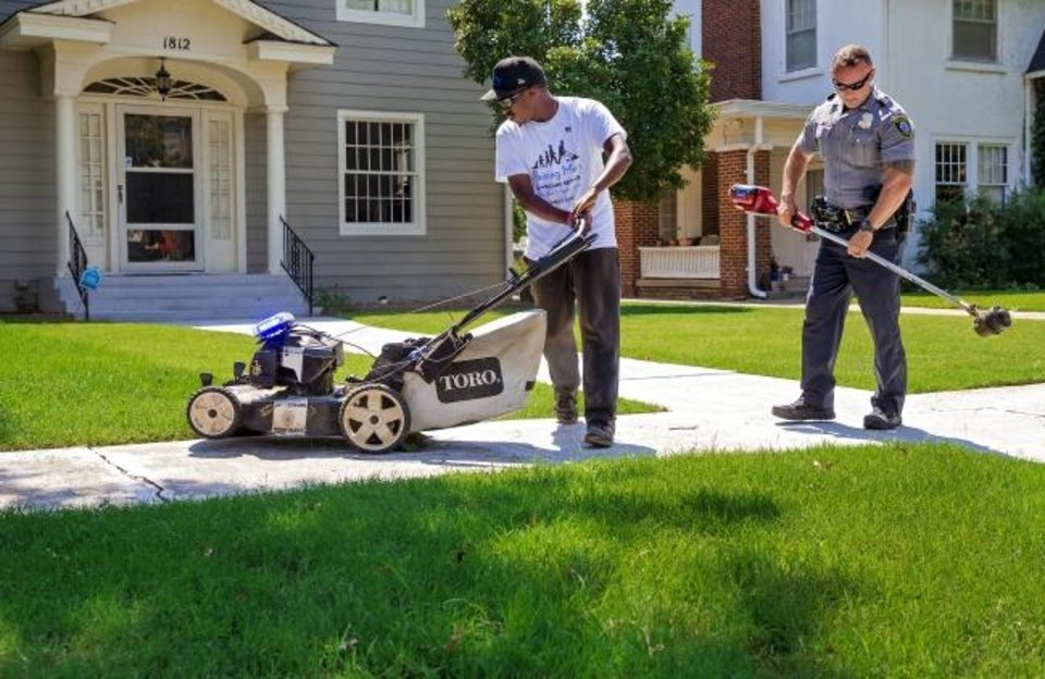 Photo -  Rodney Smith and Oklahoma City Police Department's Lt. Taylor Shaw do yard work together at a home as part of a program Smith created called Raising Men Lawn Care Service. Smith's program centers around helping elderly, disadvantaged, disabled and veterans with yard work in all 50 states. [Chris Landsberger/The Oklahoman]