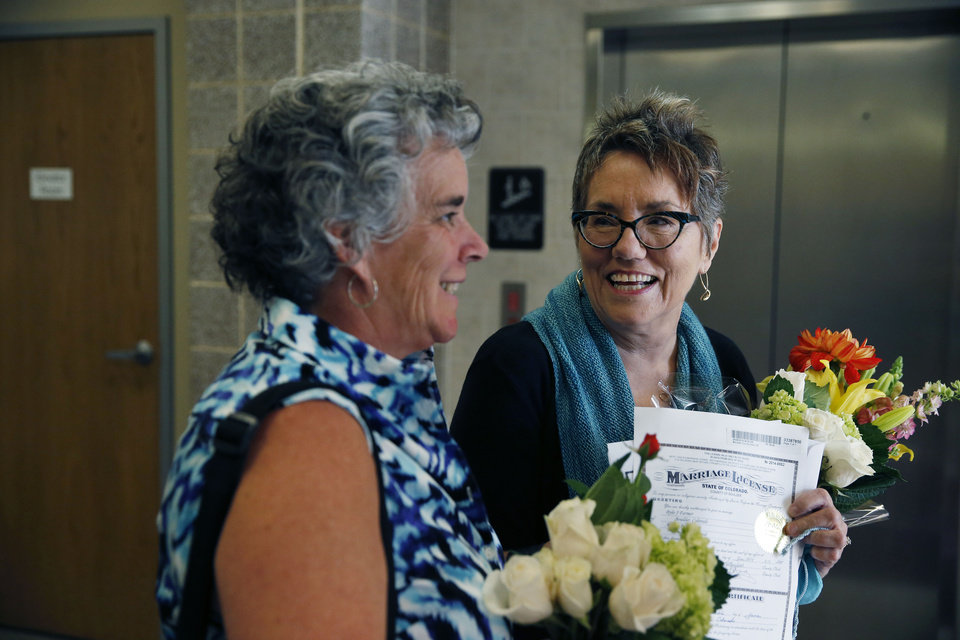 Photo - Longtime same-sex couple Angie Holley, right, and Bylo Farmer smile and carry their new marriage license, as they depart the offices of the Boulder County Clerk and Recorder, in Boulder, Colo., Thursday, June 26, 2014. Together eight years already, Holley and Farmer decided to become officially married after Boulder County Clerk Hillary Hall began issuing licenses a day earlier following a federal appeals court ruling that Utah's same-sex marriage ban is unconstitutional. (AP Photo/Brennan Linsley)