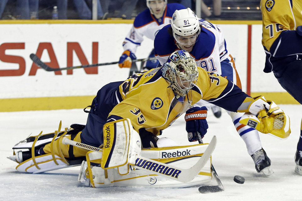 Photo - Nashville Predators goalie Pekka Rinne (35), of Finland, dives on the puck as Edmonton Oilers left wing Magnus Paajarvi (91), of Sweden, reaches for it in the first period of an NHL hockey game on Monday, March 25, 2013, in Nashville, Tenn. (AP Photo/Mark Humphrey)