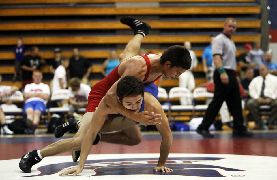 Jemuel Duran from OKC Southeast (top, red) takes down Patrick O'Brien of Tulsa Edison (right, blue) at the 2012 All State wrestling match that was held at Bixby High School on July 25, 2012. KT KING/Tulsa World