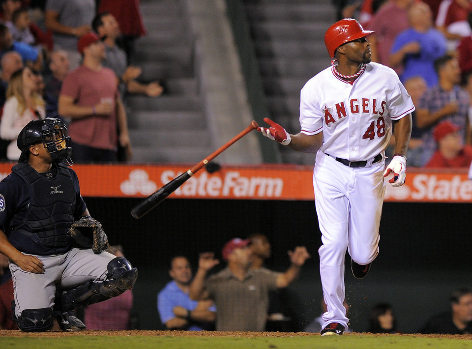 Photo -   FILE - This Sept. 25, 2012 file photo shows Los Angeles Angels' Torii Hunter, right, dropping his bat as he hits a two-run home run as Seattle Mariners catcher Miguel Olivo looks on during the fifth inning of their baseball game against the Seattle Mariners in Anaheim, Calif. A person with knowledge of the negotiations says free agent outfielder Hunter has agreed to a two-year deal with the Detroit Tigers. The person, who spoke Wednesday, Nov. 14, 2012, on condition of anonymity because no announcement has been made, says the deal is pending a physical. (AP Photo/Mark J. Terrill, File)