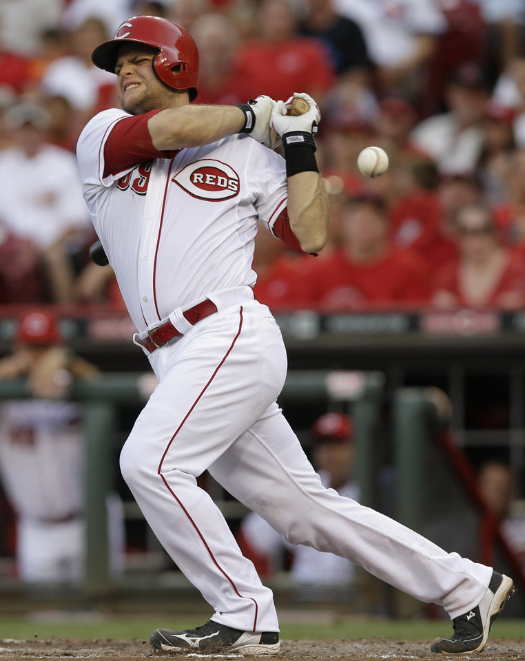 Photo - Cincinnati Reds' Devin Mesoraco grimaces as he fouls a ball of his foot in the fourth inning of a baseball game against the Chicago Cubs, Wednesday, July 9, 2014, in Cincinnati. Mesoraco fouled out to third in the at bat. (AP Photo/Al Behrman)