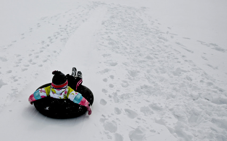 Photo - Natalyn Varney, 5, slides down a hill after a snow storm in Oklahoma City, Tuesday, Feb. 1, 2011.  Photo by Bryan Terry, The Oklahoman