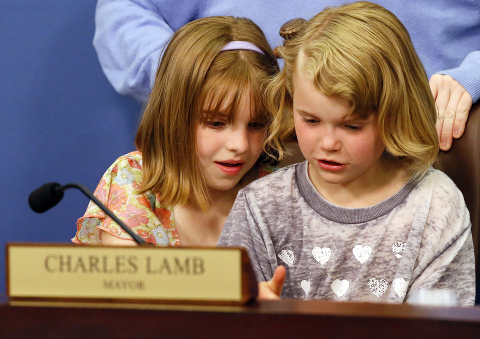 Photo - Alexandra Austin, 10, left, and Ava Lamb, 6, sit in their grandfather's chair before Edmond Mayor Charles Lamb took the oath of office. PHOTO BY NATE BILLINGS, THE OKLAHOMAN.  NATE BILLINGS - THE OKLAHOMAN