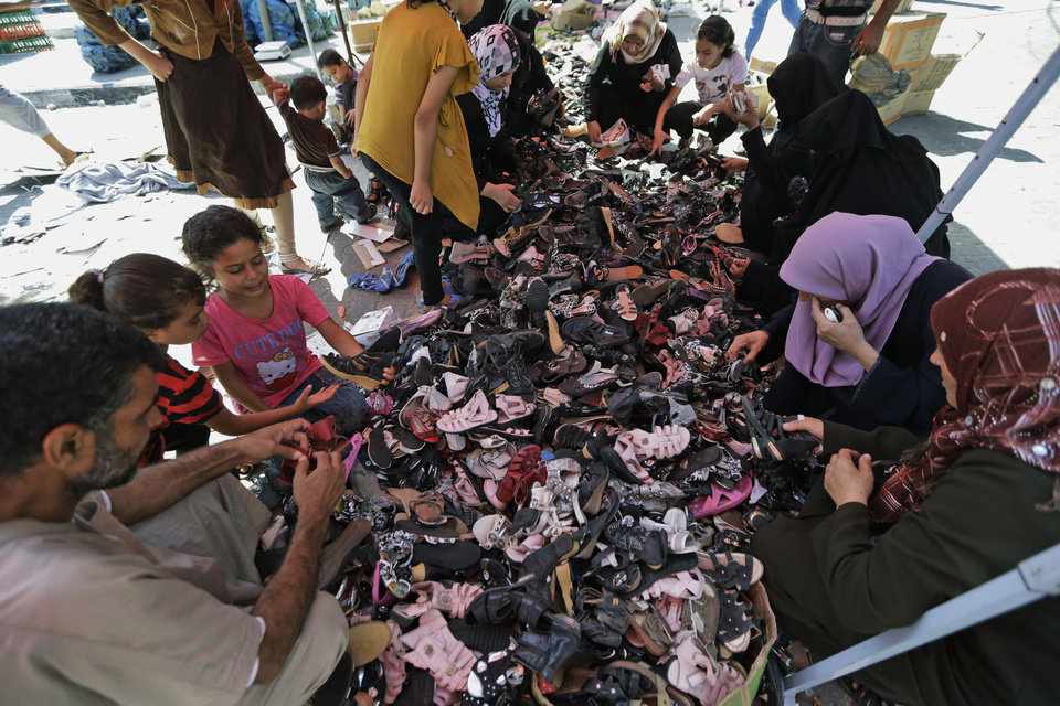 Photo - Palestinian women and children search shoes at a stall in Jebaliya refugee camp's market, northern Gaza Strip, Sunday, July 27, 2014. During normal times, families in Gaza would be busy now with preparations for Eid al-Fitr, the three-day holiday marking the end of the Muslim fasting month of Ramadan. Traditionally, children get new clothes, shoes and haircuts, and families visit each other. In the outdoor market, vendors set up stands with clothes and shoes, but said business was slow. (AP Photo/Lefteris Pitarakis)