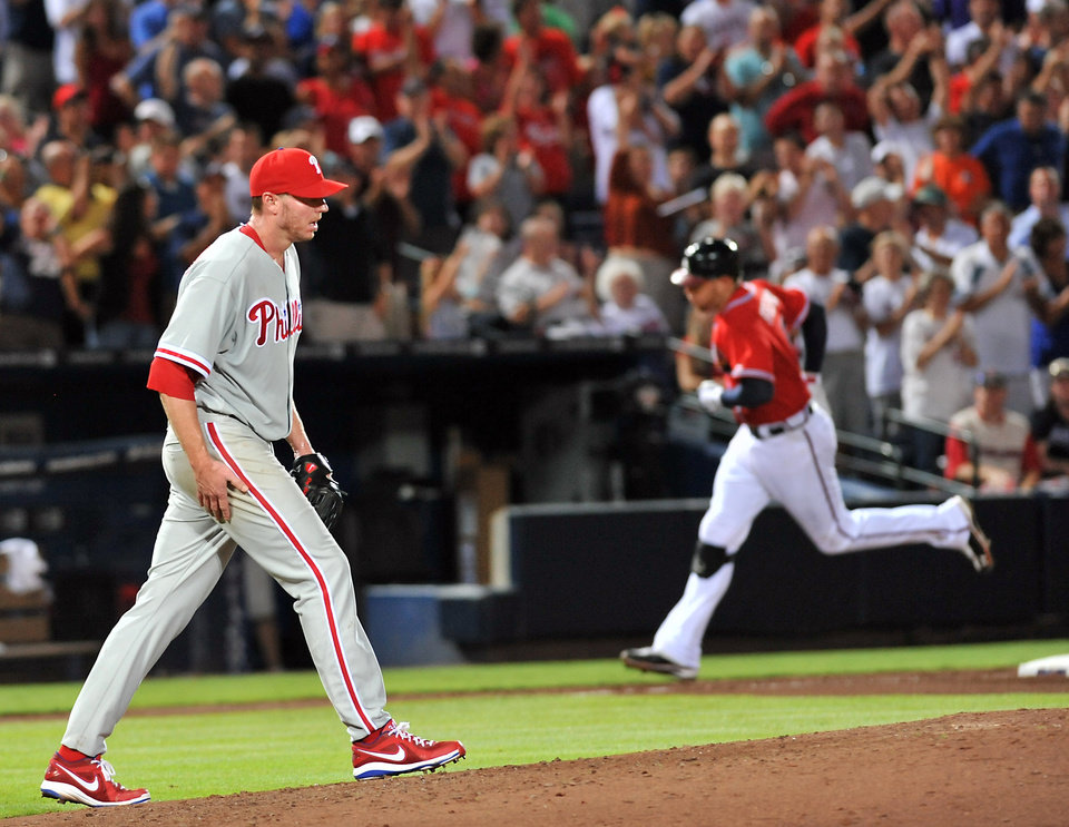 Photo -   Philadelphia Phillies starter Roy Halladay, left, walks back to the mound as Atlanta Braves' Freddie Freeman, right, rounds the bases after hitting a two-run home run during the fifth inning of a baseball game on Friday, Aug. 31, 2012, at Turner Field in Atlanta. (AP Photo/Gregory Smith)