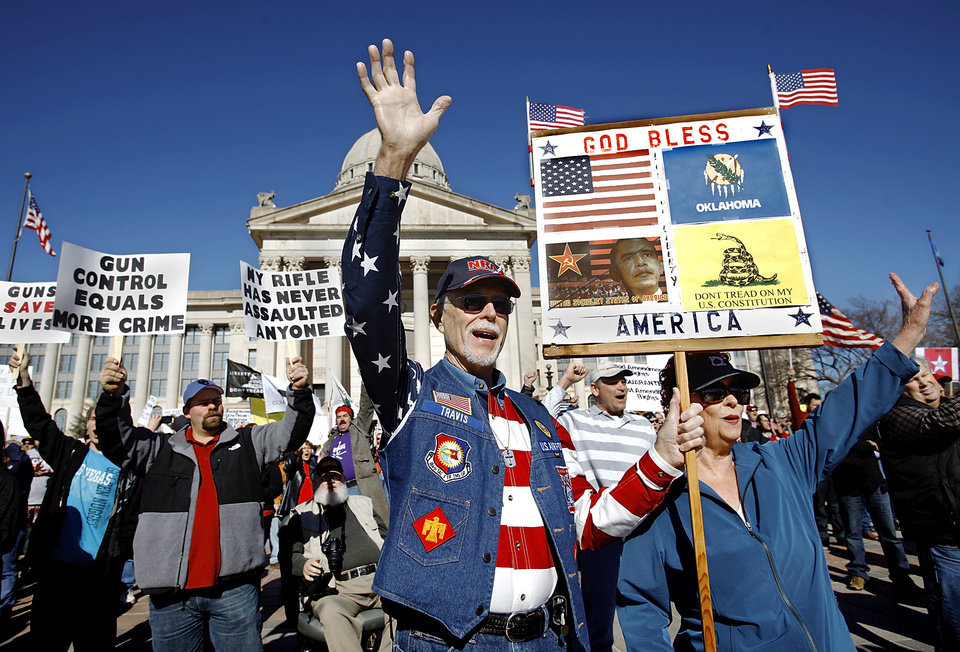 Ted Travis of Guthrie, Okla.,  joins others in the crowd in a group wave as rally participants pose for a group picture as the rally concludes. Organizers said an estimated 1800 people from throughout Oklahoma crowded into the south plaza at the state Capitol Saturday afternoon, Jan. 19, 2013, to voice their support for their second amendment rights and to express  concerns about proposed gun control legislation being considered by the federal government in the wake of the school shooting in Connecticut last month. Many  held aloft hand-made signs or waved American flags as speakers addressed the gun rights rally.  Travis attended with his wife. He said he created the sign he holds. Photo by Jim Beckel, The Oklahoman