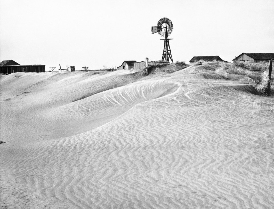 Photo -  This March 29, 1937, photo shows rippling dunes banked against a fence, farm home, barn and windmill in Guymon, OK. The property was abandoned by its owner when destructive dust clouds forced him to leave.  AP File Photo    -  AP