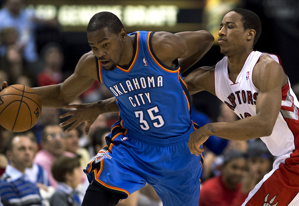 Photo - Toronto Raptors guard DeMar DeRozan, right, tries to strip the ball from Oklahoma City Thunder forward Kevin Durant (35) during the first half of NBA basketball game action in Toronto on Sunday, Jan. 6, 2013. (AP Photo/The Canadian Press, Frank Gunn)  ORG XMIT: FNG101