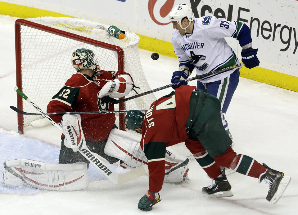 Vancouver Canucks' Dale Weise, right, has a shot on-goal deflected by Minnesota Wild goalie Niklas Backstrom, of Finland, in the first period of an NHL hockey game on Thursday, Feb. 7, 2013, in St. Paul, Minn. (AP Photo/Jim Mone)
