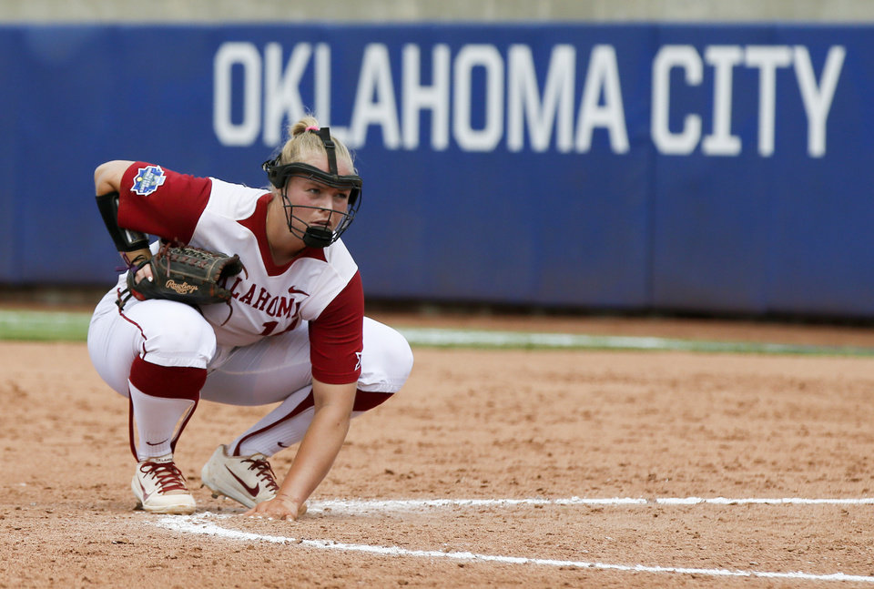 Photo - Oklahoma's Paige Lowary (14) touches the ground before throwing a pitch in the top of the fifth inning during the second game of the Women's College World Series between the Oklahoma Sooners (OU) and Washington Huskies at USA Softball Hall of Fame Stadium in Oklahoma City, Thursday, May 31, 2018. Washington won 2-0. Photo by Nate Billings, The Oklahoman
