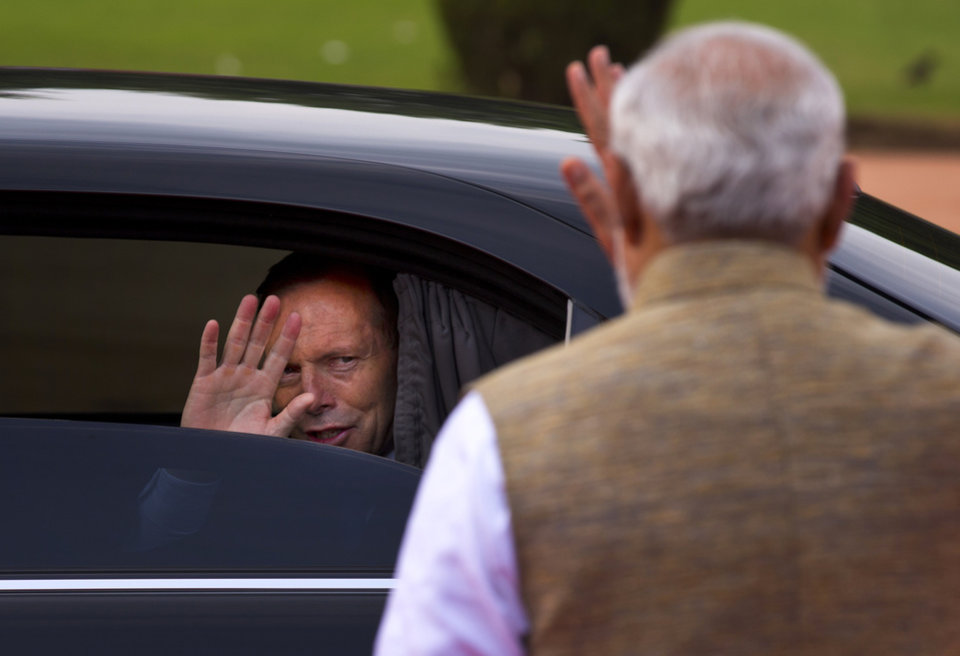 Photo - Australian Prime Minister Tony Abbott, left, waves at his Indian counterpart Narendra Modi as he leaves after a ceremonial welcome in New Delhi, India, Friday, Sept. 5, 2014. Abbott is on a two-day visit to India. (AP Photo/Saurabh Das)