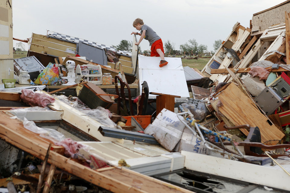 Photo - Campbell Miller, 10, looks through the home of his grandmother, Marlena Hodson, after a tornado damaged her home in Carney Okla., Sunday, May 19, 2013. Hodson and her family left the home to escape the tornado. Photo by Bryan Terry, The Oklahoman