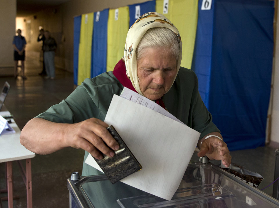 Photo - An elderly woman casts her vote in the presidential election in the eastern town of Krasnoarmeisk, Ukraine, Sunday, May 25, 2014. Ukraine's critical presidential election got underway Sunday under the wary scrutiny of a world eager for stability in a country rocked by a deadly uprising in the east. While there were no immediate reports of violence, pro-Russia insurgents were trying to block voting by snatching ballot boxes and patrolling polling stations.(AP Photo/Vadim Ghirda)