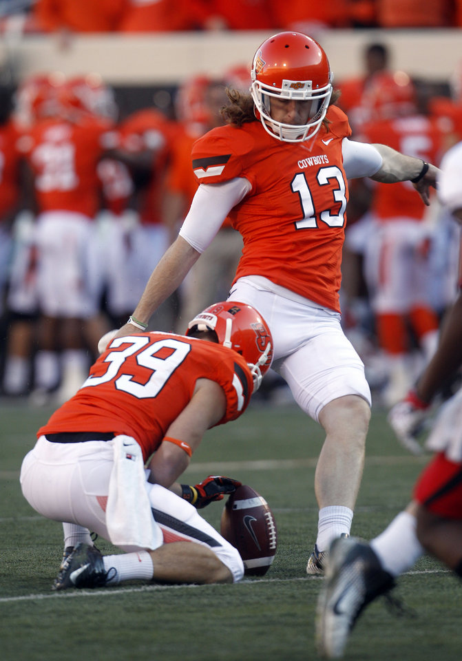 Oklahoma State kicker Quinn Sharp (13) boots an extra point against Texas Tech as Wes Harlan (39) holds in the second quarter of an NCAA college football game in Stillwater, Okla., Saturday, Nov. 17, 2012. (AP Photo/Sue Ogrocki)