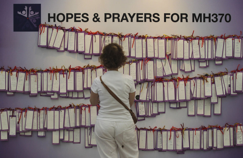 Photo - A woman read message cards tied up for passengers aboard a missing Malaysia Airlines plane, at a shopping mall in Kuala Lumpur, Malaysia, Monday, March 24, 2014. A Chinese plane on Monday spotted two white, square-shaped objects in an area identified by satellite imagery as containing possible debris from the missing Malaysian airliner, while the United States separately prepared to send a specialized device that can locate black boxes. (AP Photo)