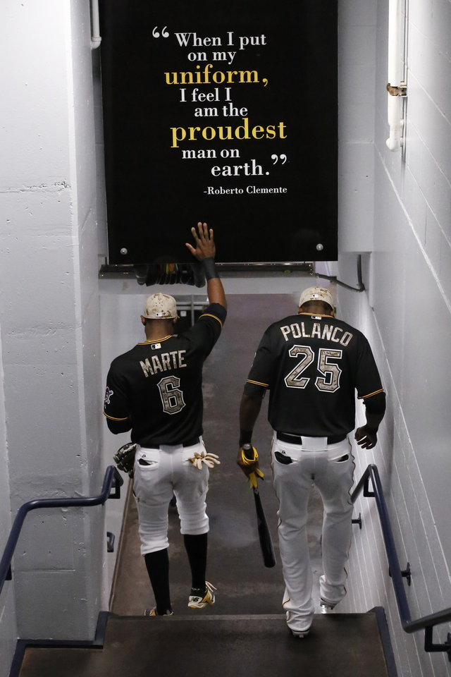 Photo - Pittsburgh Pirates' Gregory Polanco (25) and teammate Starling Marte (6) walk to the dugout before a baseball game against the Chicago Cubs in Pittsburgh Tuesday, June 10, 2014. Polanco is making his first start in the Major Leagues. (AP Photo/Gene J. Puskar)