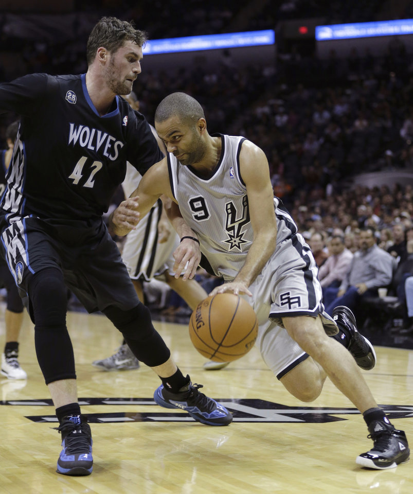 Photo - San Antonio Spurs' Tony Parker (9), of France, drives around Minnesota Timberwolves' Kevin Love (42) during the first half on an NBA basketball game, Sunday, Jan. 12, 2014, in San Antonio.  (AP Photo/Eric Gay)