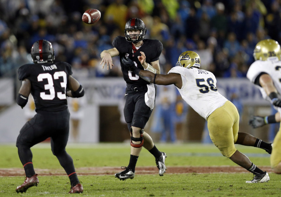 Photo - Stanford quarterback Kevin Hogan throws under pressure from UCLA defensive end Datone Jones (56) during the first half of the Pac-12 championship NCAA college football game in Stanford, Calif., Friday, Nov. 30, 2012. (AP Photo/Marcio Jose Sanchez)