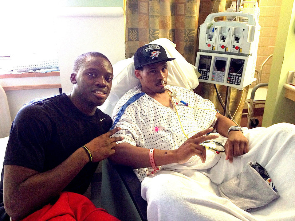 Photo - Thunder reserve guard Reggie Jackson visits with Bricktown shooting victim Norman Richards II at OU Medical Center in early June.  PROVIDED