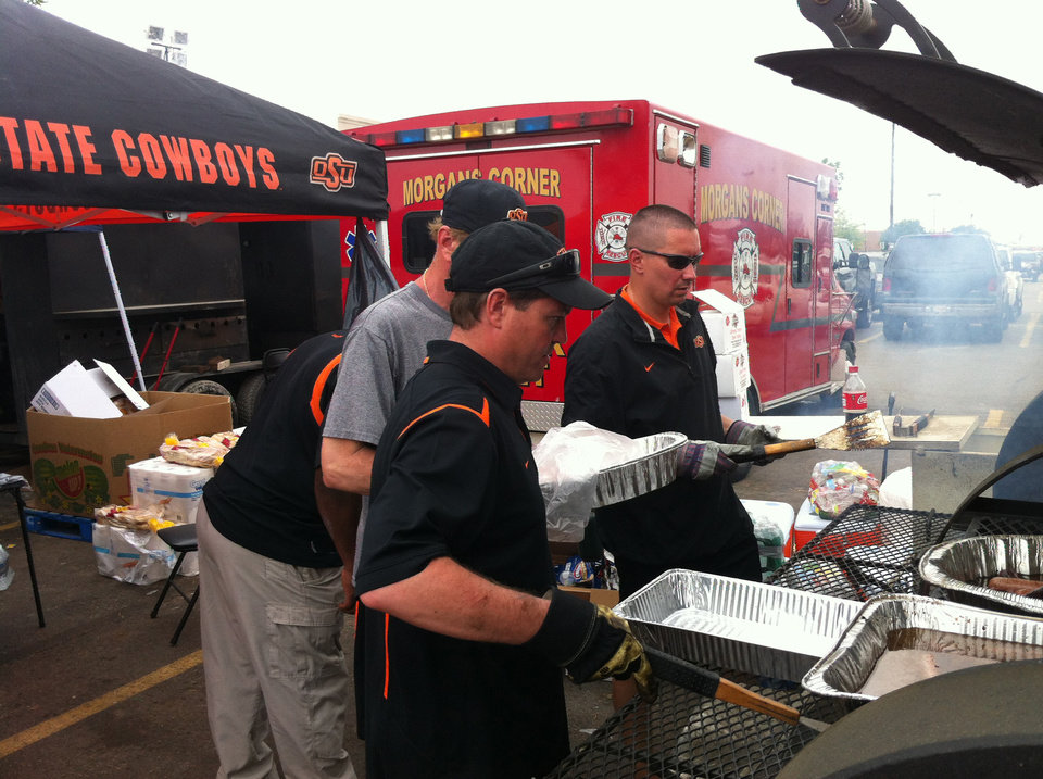 Photo - From left, OSU basketball coach Travis Ford, Tommy Wade, OSU's director of player development, and Lt. Leon Jones of the OSU Police Department help cook hamburgers in the parking lot of the Home Depot in Moore on Friday. PHOTO BY BERRY TRAMEL, THE OKLAHOMAN KOD