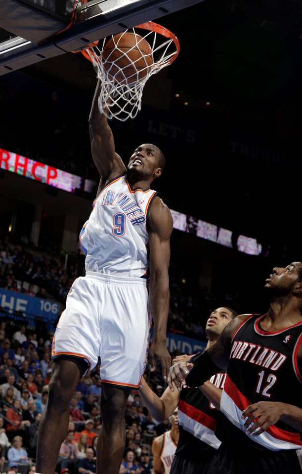 Oklahoma City's Serge Ibaka (9) dunks the ball in front of Portland 's LaMarcus Aldridge (12) during the NBA basketball game between the Oklahoma City Thunder and the Portland Trailblazers at Chesapeake Energy Arena in Oklahoma City, Sunday, March 18, 2012. Photo by Sarah Phipps, The Oklahoman.