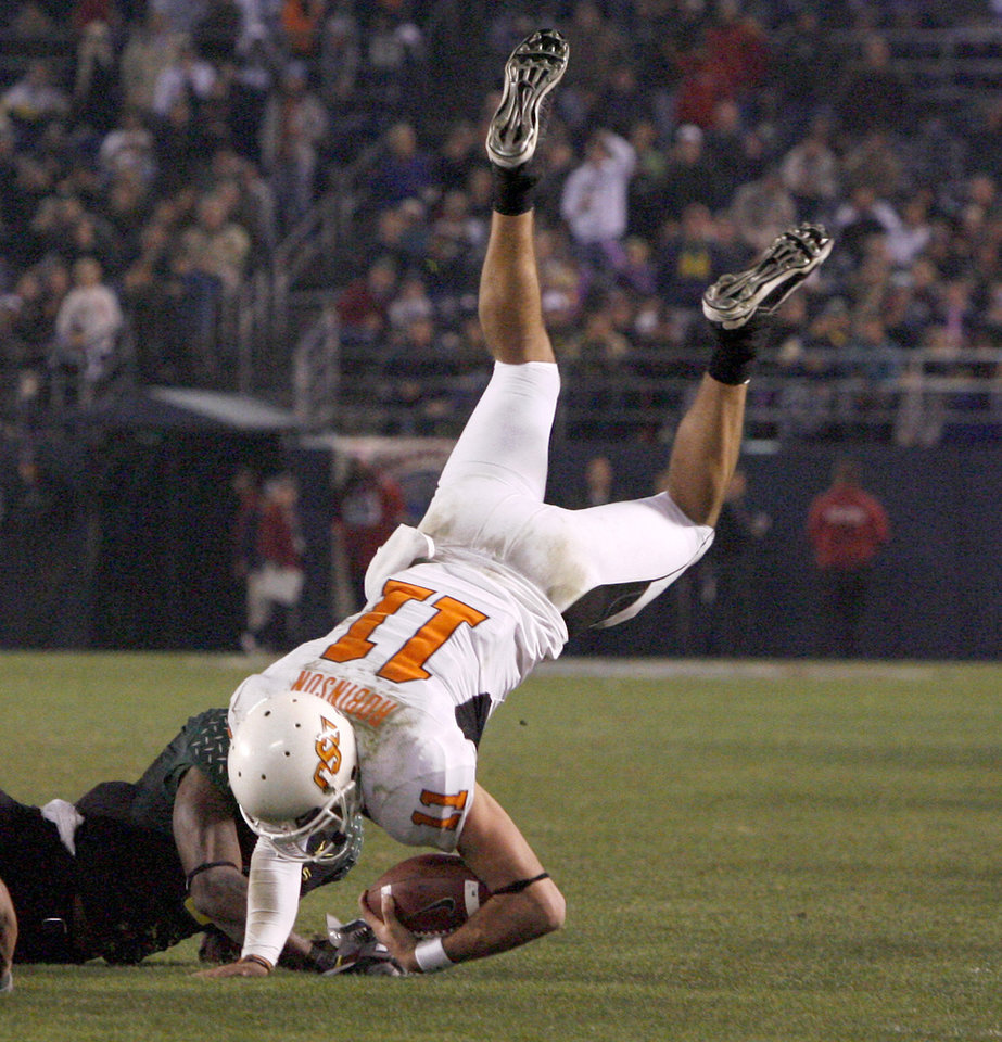 Photo - OSU's Zac Robinson is brought down after catching a pass by Bo Bowling during the Holiday Bowl college football between Oklahoma State and Oregon at Qualcomm Stadium in San Diego, Tuesday, Dec. 30, 2008.  PHOTO BY BRYAN TERRY, THE OKLAHOMAN.