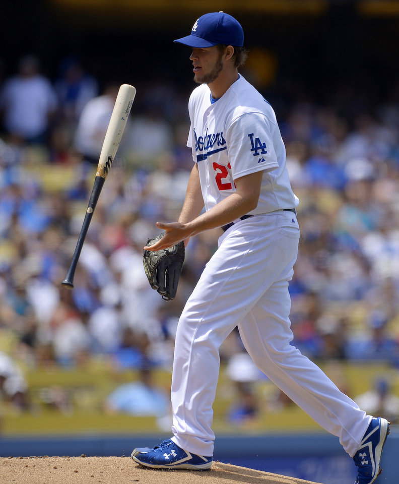 Los Angeles Dodgers starting pitcher Clayton Kershaw flips a bat that was accidentally thrown toward him by St. Louis Cardinals' Yadier Molina during the third inning of a baseball game on Sunday, May 26, 2013, in Los Angeles. (AP Photo/Mark J. Terrill)