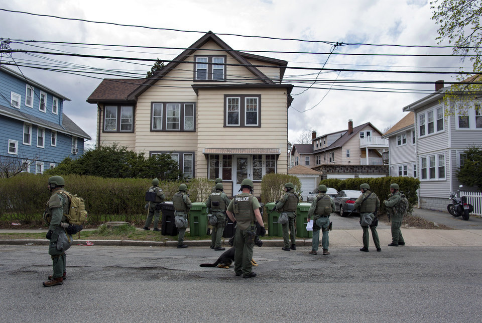 Heavily armed police officers do house to house searches in the neighborhoods of Watertown, Mass. Friday, April 19, 2013, as a massive search continued for one of two suspects in the Boston Marathon bombing. A second suspect died in the early morning hours after an encounter with law enforcement. (AP Photo/Craig Ruttle) ORG XMIT: MACC120