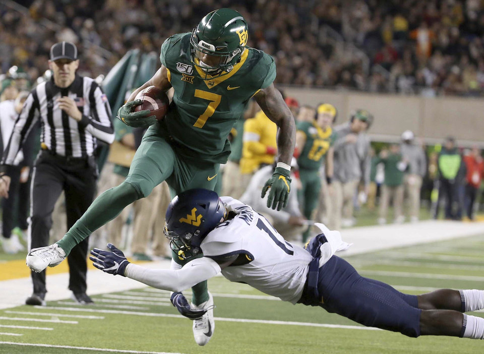 Photo - Baylor running back John Lovett (7) is tackled by West Virginia safety Kerry Martin Jr. (15) during the first half of an NCAA college football game in Waco, Texas, Thursday, Oct. 31, 2019. (AP Photo/Jerry Larson)