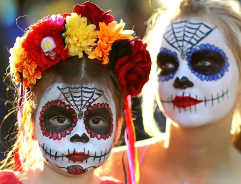 Photo -  Sisters Sophia Beitia, 3, and Becca Spears, 16, of Edmond, are pictured during the Day of the Dead Festival in the Plaza District on Sunday. [DOUG HOKE/THE OKLAHOMAN]