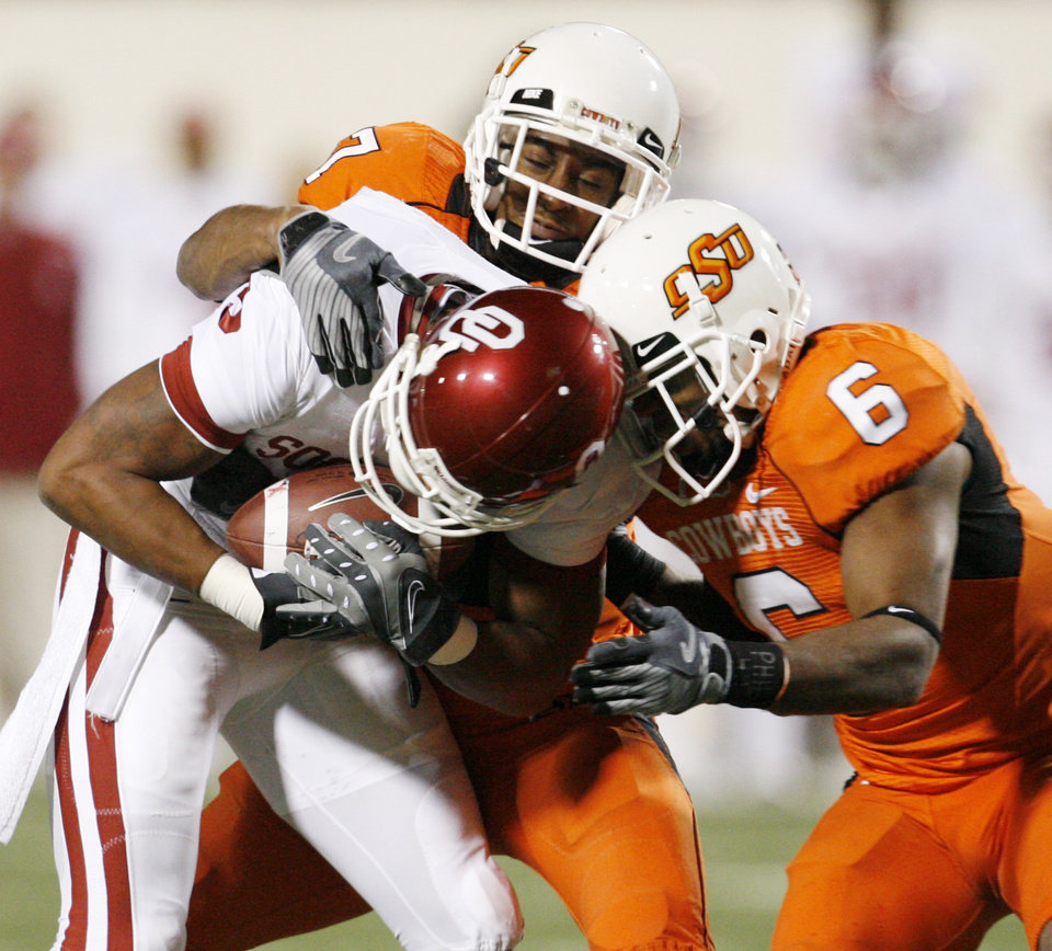Juaquin Iglesias is stopped after a catch by Maurice Gray (7) and Rickey Price (6) during the first half of the college football game between the University of Oklahoma Sooners (OU) and Oklahoma State University Cowboys (OSU) at Boone Pickens Stadium on Saturday, Nov. 29, 2008, in Stillwater, Okla. STAFF PHOTO BY NATE BILLINGS