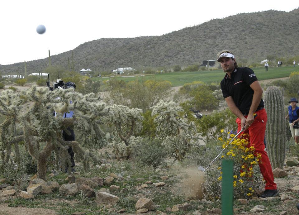 Photo - Victor Dubuisson, of France, hits out of the desert on the 20th hole in his championship match against Jason Day, of  Australia, during the Match Play Championship golf tournament on Sunday, Feb. 23, 2014, in Marana, Ariz. (AP Photo/Ted S. Warren)