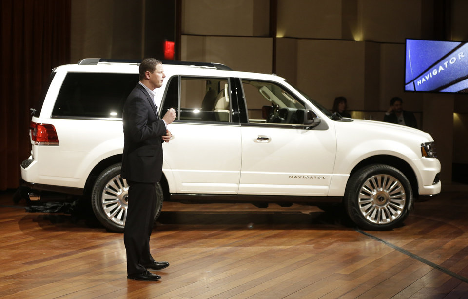 Photo - Andrew Frick, Lincoln Motor Co's, marketing manager stands next to the new new 2015 Lincoln Navigator at its unveiling in Detroit, Tuesday, Jan. 21, 2014. Lincoln Motor Co. _ Ford's luxury arm _ says the new Navigator will have more than 20 upgrades, from bigger wheels and a leather-wrapped steering wheel to a 3.5-liter EcoBoost V6 engine to replace its old V8. Lincoln plans to publicly unveil the vehicle at the Chicago Auto Show. The SUV _ which will be built in Kentucky _ goes on sale this fall. (AP Photo/Carlos Osorio)