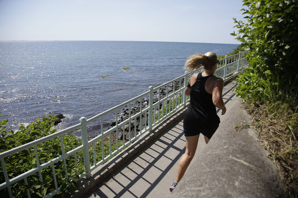 Photo - A jogger runs along the Newport Cliff Walk Tuesday, June 24, 2014 in Newport, RI. Parts of the well known attraction were damaged by Superstorm Sandy in 2012 and official reopened in a ribbon cutting ceremony.   The storm washed away and damaged several sections of the walk, and most of it has been closed since the 2012 storm.  (AP Photo Stephan Savoia)