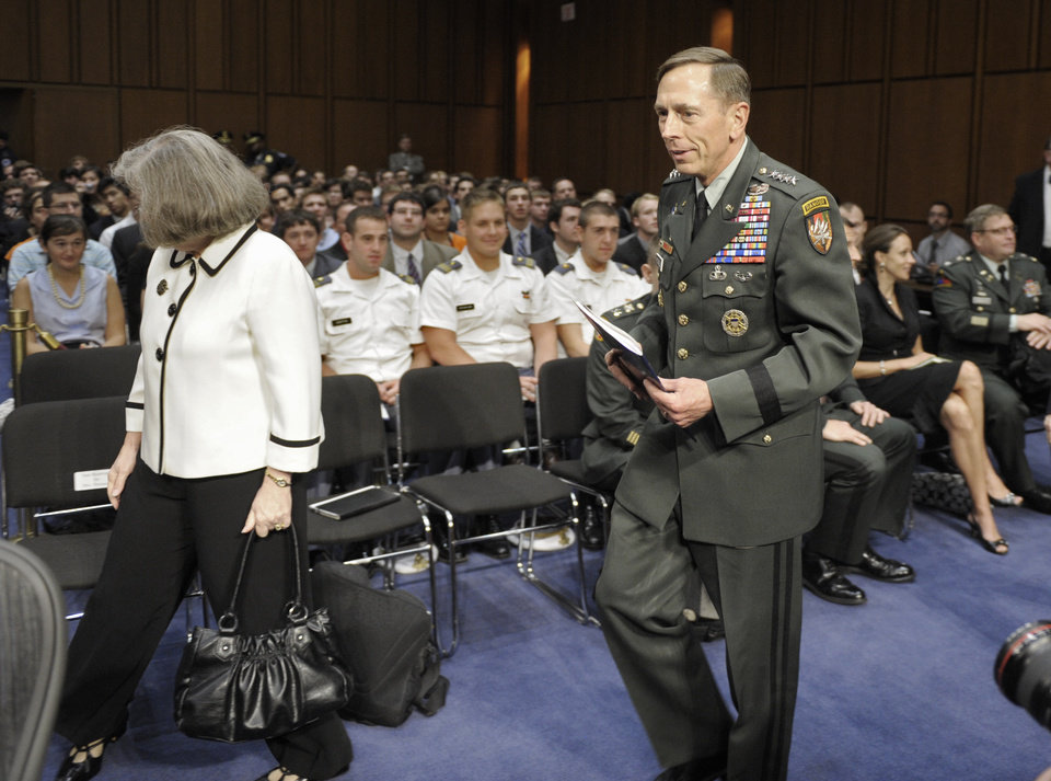 FILE - In this June 23, 2011, file photo, Gen. David Petraeus, center, walks with his wife Holly, left, past a seated Paula Broadwell, rear right, as he arrives to appear before the Senate Intelligence Committee during a hearing on his nomination to be Director of the Central Intelligence Agency on Capitol Hill in Washington. Petraeus quit Nov. 9, 2012, after acknowledging an extramarital relationship. As questions arise about the extramarital affair between Petraeus and his biographer, Paula Broadwell, she has remained quiet about details of their relationship. However, information has emerged about Jill Kelley, the woman who received the emails from Broadwell that led to the FBI�s discovery of Petraeus� indiscretion. (AP Photo/Cliff Owen, File)