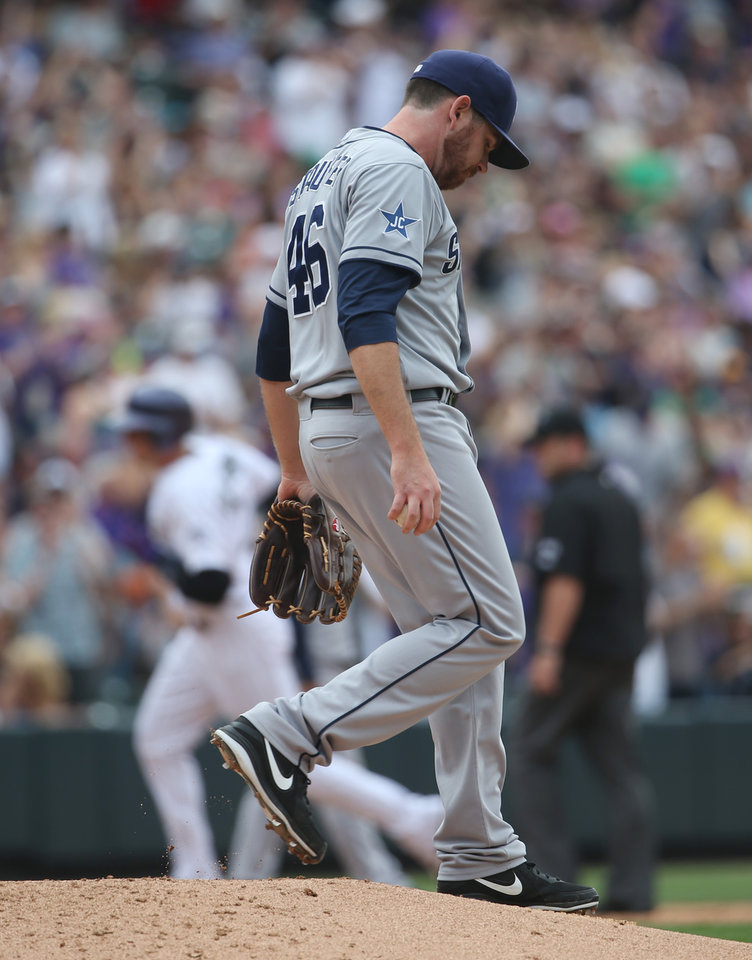 Photo - San Diego Padres relief pitcher Tim Stauffer, front, reacts after giving up a solo home run to Colorado Rockies' Troy Tulowitzki, back, in the fifth inning of a baseball game in Denver on Sunday, May 18, 2014. (AP Photo/David Zalubowski)