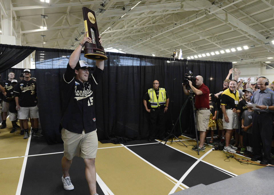 Photo - Vanderbilt pitcher Carson Fulmer hoists the NCAA College World Series trophy as he is introduced during a victory celebration for the team's first baseball national championship at Vanderbilt University on Thursday, June 26, 2014, in Nashville, Tenn.  (AP Photo/Mark Zaleski)
