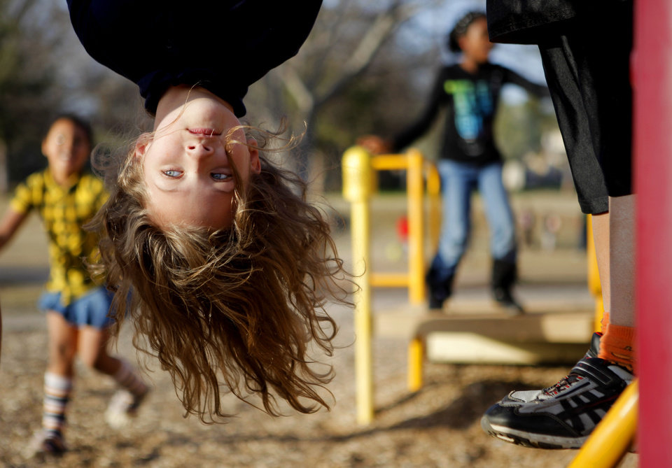 Photo - Kammi Burgess, 7, hangs upside down on playground equipment at the Boys and Girls Club of Oklahoma City. Photo by Bryan Terry, The Oklahoman