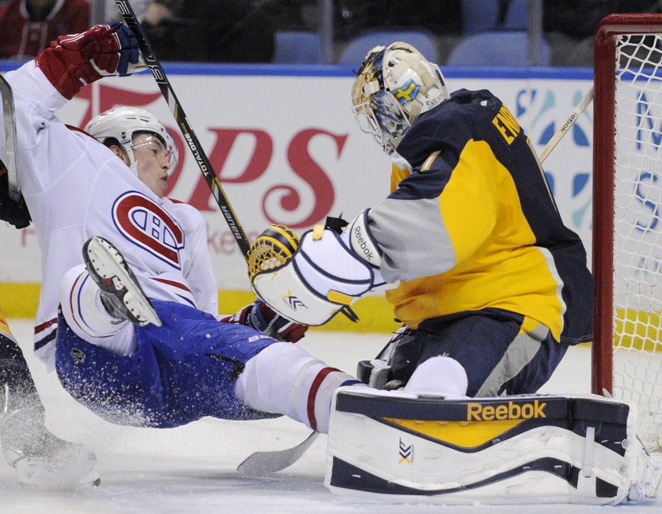 Photo - Montreal Canadiens right winger Brendan Gallagher, left, crashes into Buffalo Sabres goaltender Jhonas Enroth during the second period of an NHL hockey game in Buffalo, N.Y., Sunday, March 16, 2014. Enroth was injured and left the game. Montreal won 2-0. (AP Photo/Gary Wiepert)