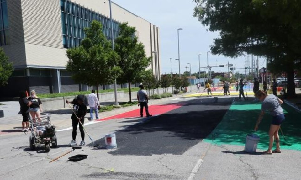 Photo -  People work to paint portions of Shartel Avenue, next to the Oklahoma City police headquarters on Tuesday. [Doug Hoke/The Oklahoman]